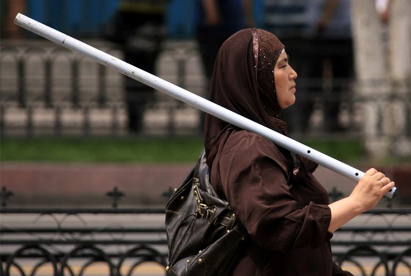 A Uyghur woman carrying a metal rod for protection from attacks. This has become common practice amongst Uyghur women.
